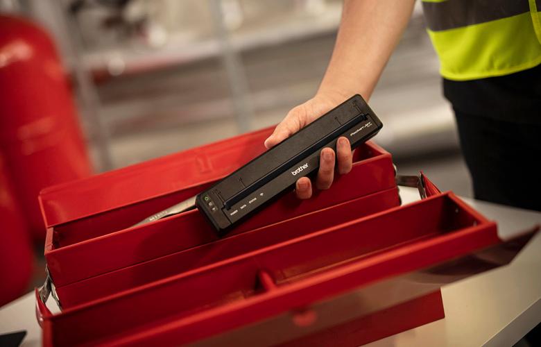 Pracovník vrací zpět černou PJ tiskárnu do červené přepravky