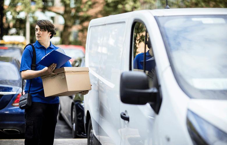 A futár dobozt és dokumentumokat tart a kezében, az RJ nyomtató vállpánton lóg a válláról, egy fehér kisteherautó mellett