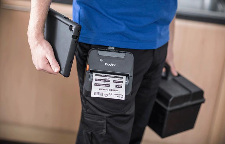 Robotnik w niebieskim t-shircie, trzyma skrzynkę i tablet, drukarka RJ jest przyczepiona do paska