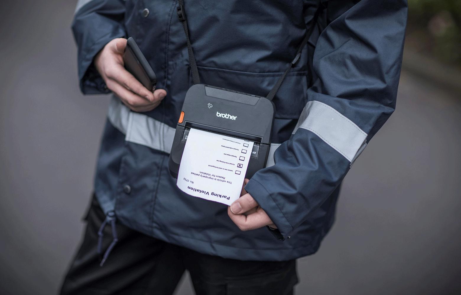 Zaposlenik na parkiralištu ispisuje parkirnu kartu na RJ pisaču na ramenskoj traci