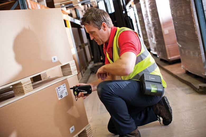 Служител в склад сканира етикет на кашон с RJ принтер на щипка за колан