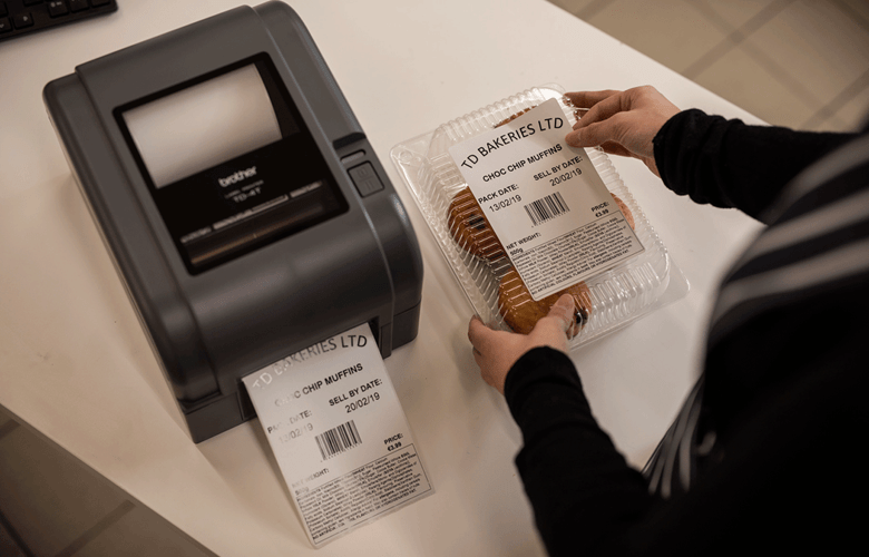Етикетен принтер серия TD, служител лепи отпечатан етикет на кутия с кифли