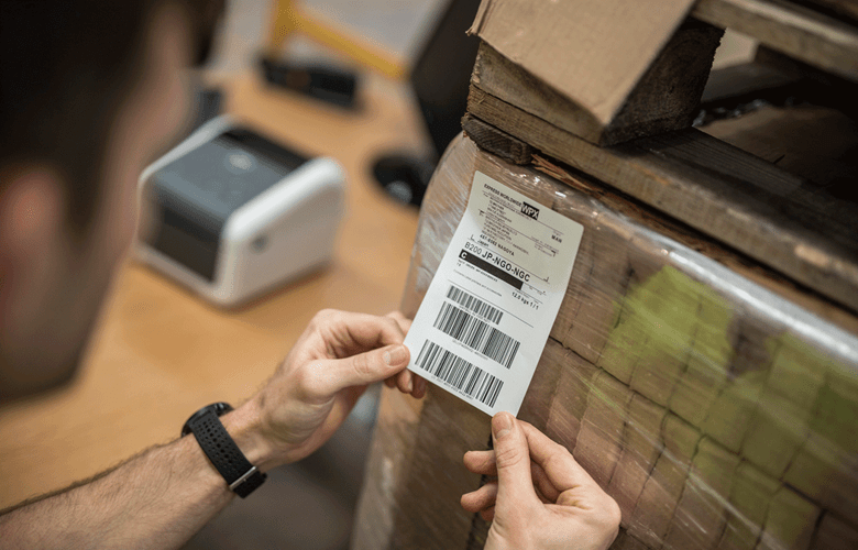 Мъж етикетира кутия с етикет за доставка