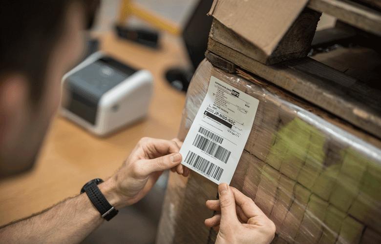 muž označujúci krabice prepravnými štítkami