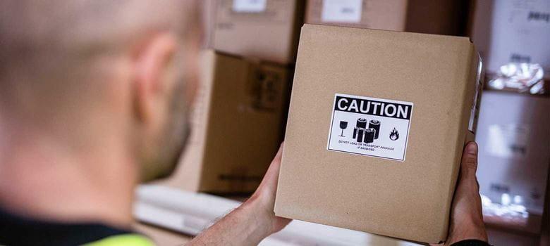 Moški drži rjavo škatlo z opozorilno nalepko v centru za obdelavo naročil