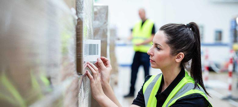 Nő, jól láthatósági mellényben vonalkódos címkét ragaszt a dobozra a teljesítési központban
