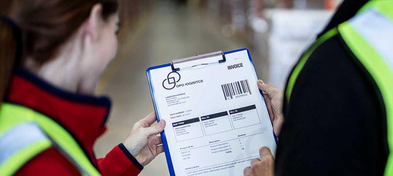 Moški in ženska v opozorilnima jopičema držita mapo z računi v skladišču