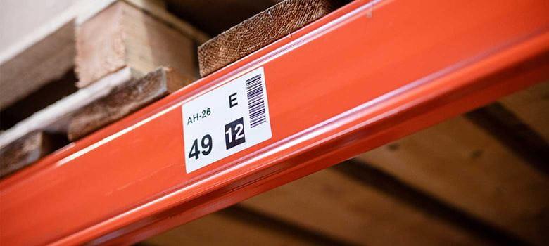 Oranžové regály s čárovým kódem a čísly na štítku ve skladu