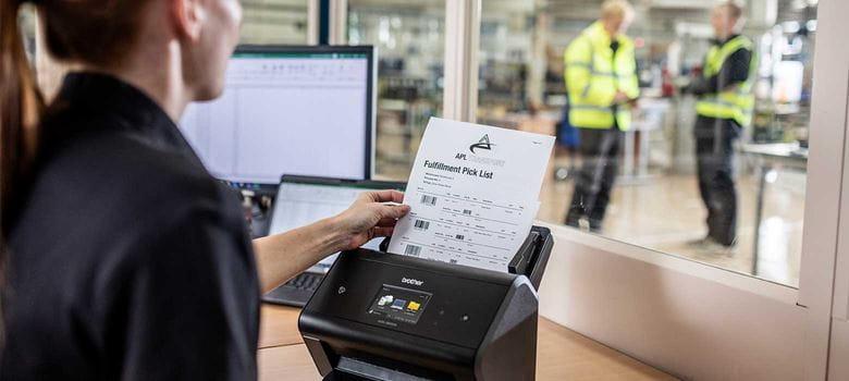 Žena v černém vkládá dokument do skeneru ve skladu s notebookem, monitorem a dalšími pracovníky