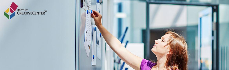 žena v pripína oznámenie na tabuľu v kancelárii
