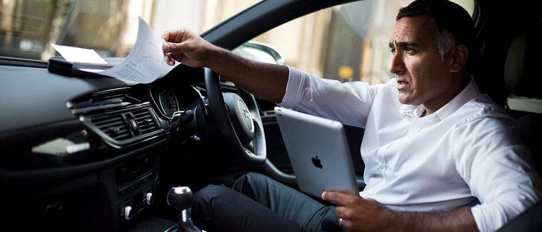 Mann druckt im Auto über Tablet ein Dokument über mobilen Drucker aus.