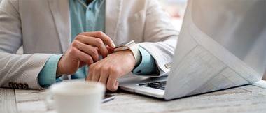 Mitarbeiter am Schreibtisch bedient seine Smartwatch.