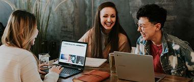 Drei Frauen sitzen am Tisch mit Laptops und lachen.