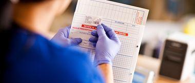 Krankenpflegerin klebt Barcode-Etikett auf Patientenakte. Etikettendrucker im Hintergrund.