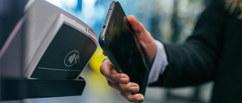 Person bezahlt per Smartphone an NFC-Terminal