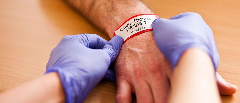 Krankenpfleger legt Patient ein Armband um