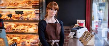 Lebensmittelverkäuferin steht neben verpackten Sandwiches.