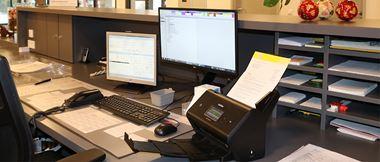 Dokumentenscanner steht auf dem Schreibtisch einer Krankenhausrezeption.