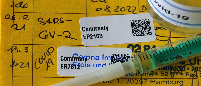 Impfpass mit Etikett von Coronaschutzimpfung, Spritze und Ampulle.