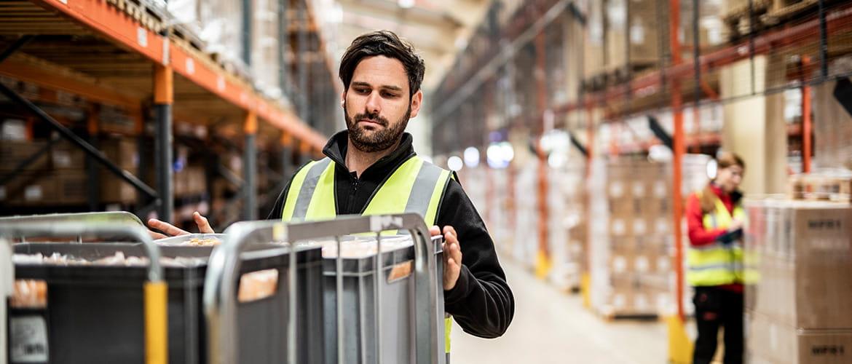 Mann in gelber Warnweste steht mit Transportwagen in einem Lagergang und pickt Waren.