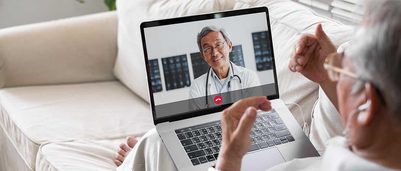 Mann mit Laptop auf dem Sofa in einer Videokonferenz mit seinem Doktor