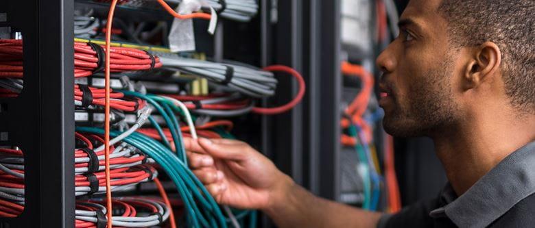 Mann untersucht Kabelstränge in einem Verteilerschrank