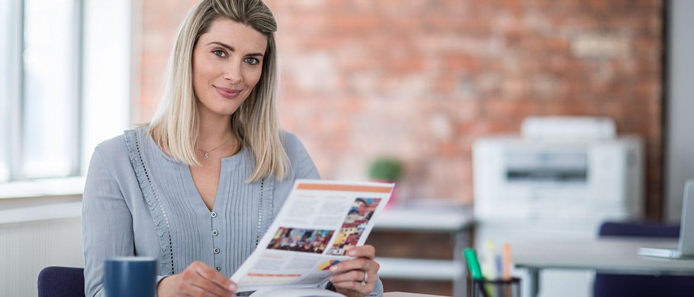 Frau in Büro hält Farbausdruck in Händen, Drucker im Hintergrund