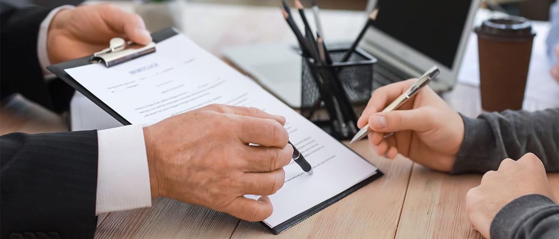 Hände einer Person halten ein Klemmbrett mit einem Dokument und zeigen den Händen einer weiteren Person wo die Unterschrift gesetzt werden soll.