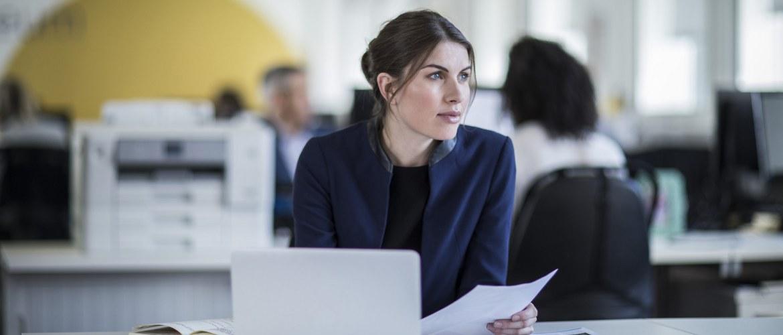 Frau im Büro hält ein Blatt Papier in der Hand und denkt nach. Drucker im Hintergrund.
