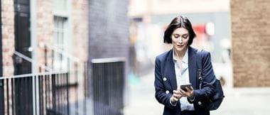 Frau geht Straße entlang und schaut auf ihr Smartphone
