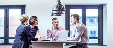 Vier Menschen sitzen an Bürotisch und diskutieren