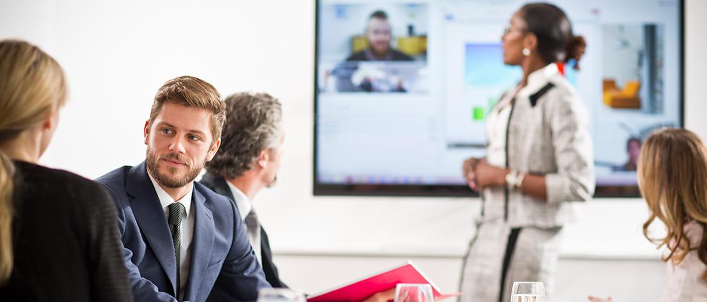 Personen in einem Meetingraum unterhalten sich über Videokonferenz.