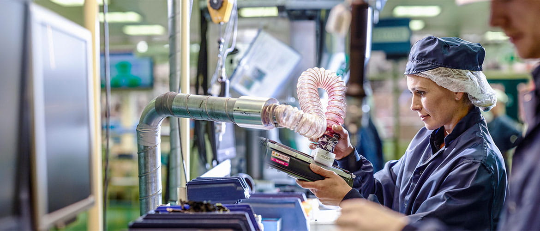 Arbeiterin an Fließband saugt Resttoner aus Kartusche