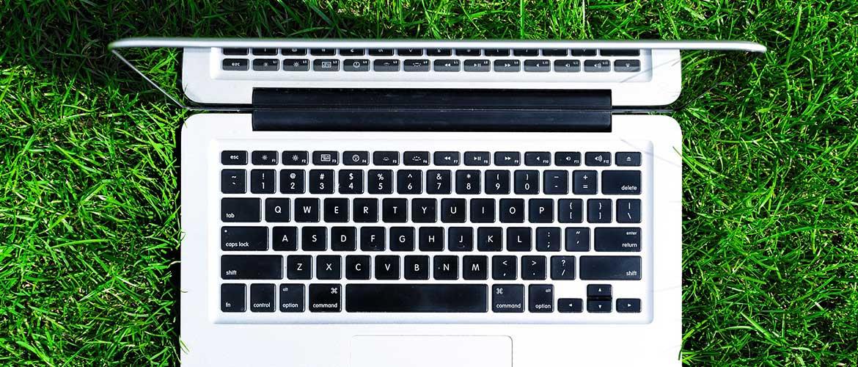 Aufgeklappter Laptop von oben, der auf einer grünen Wiese steht.