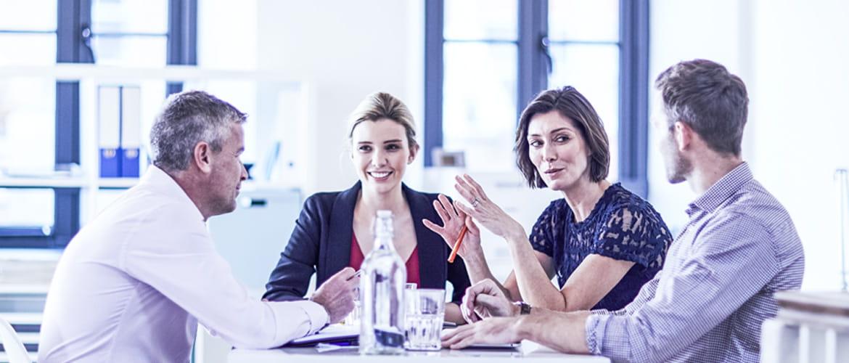 Vier Mitarbeiter diskutieren an einem Tisch