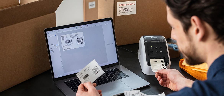 Mann druckt Versandetiketten für Pakete am Laptop über einen Etikettendrucker.