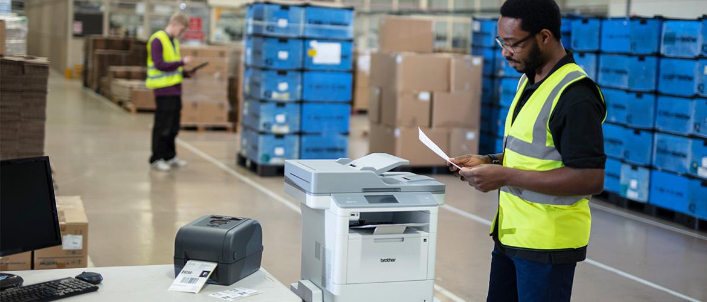 Mann in Lagerhalle hält ein Dokument in der Hand, Multifunktions- und Etikettendrucker neben ihm.