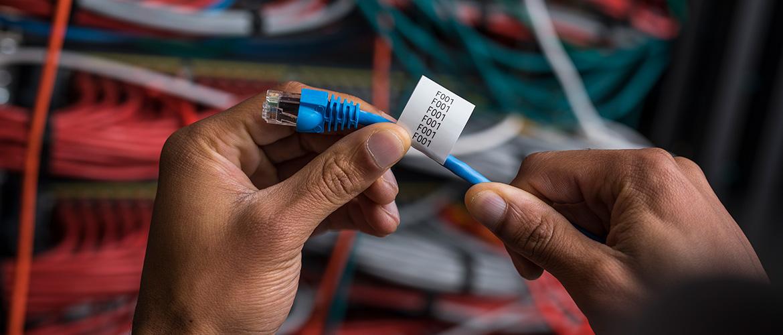 Zwei Hände kleben ein Etikett um ein Netzwerkkabel um es zu kennzeichnen.