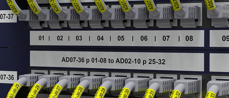 Verteilerblock mit diversen Netzwerkkabeln in Ports. Farbige Etiketten zur Kennzeichnung.