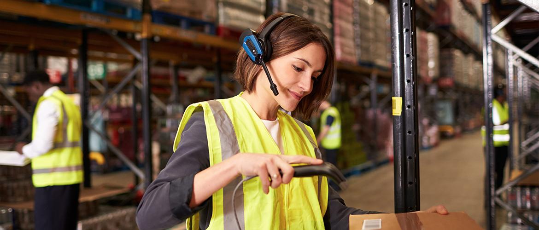 Lagerarbeiterin mit Headset scannt ein Paket an einem Regal ein.