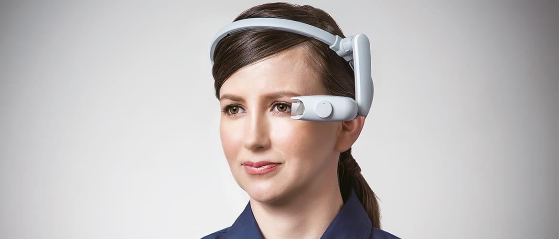 Frau trägt ein Head-Mounted-Display, das ihr Informationen direkt vor das Auge projiziert.
