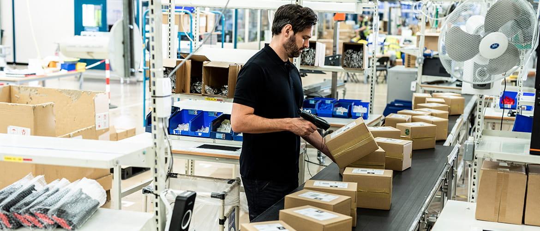 Mann an einem Förderband scannt Barcodes auf Paketen.