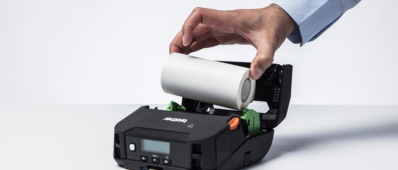Hand wechselt Papierrolle in mobilem Belegdrucker