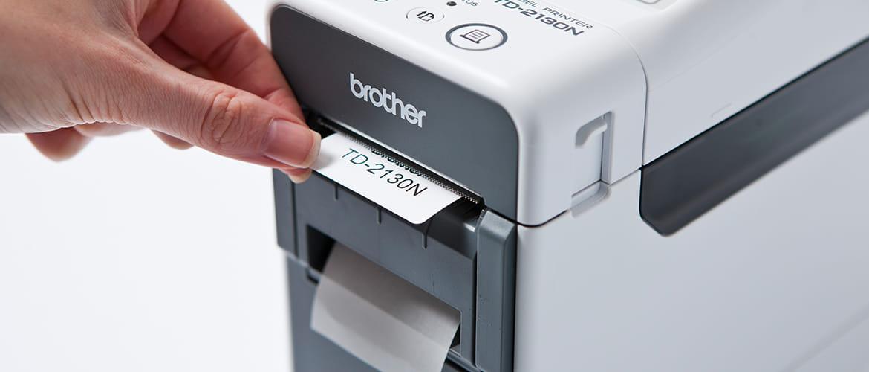 Eine Hand holt ein Klebe-Etikett aus einem Etikettendrucker von Brother.