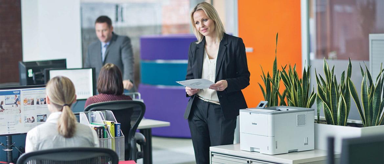 Frau holt Ausruck aus Laserdrucker im Büro