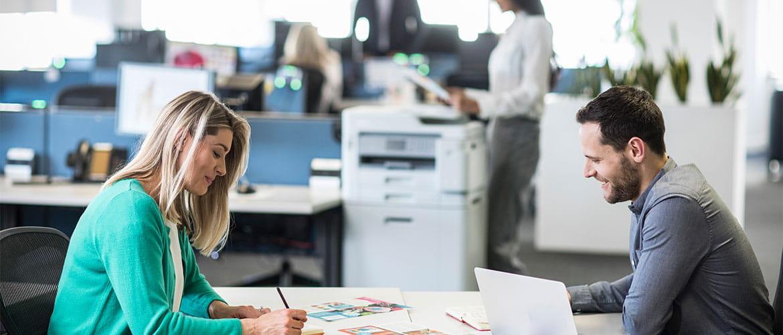 Zwei Menschen im Büro am Schreibtisch, Drucker im Hintergrund