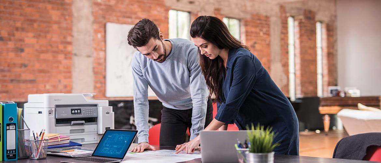 Mann und Frau betrachten ein Dokument auf einem Schreibtisch. Drucker im Hintergrund.