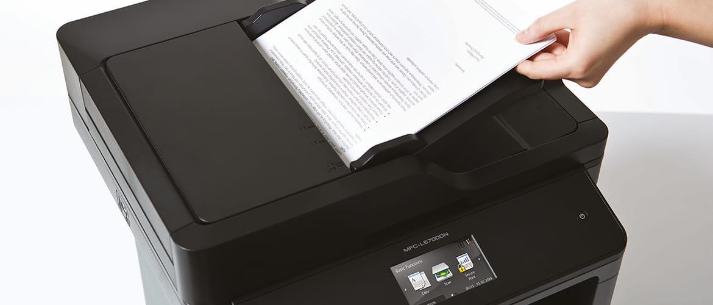 Eine Hand legt ein Papierdokument zum Scannen in den automatischen Vorlageneinzug eines Multifunktionsdruckers von Brother.