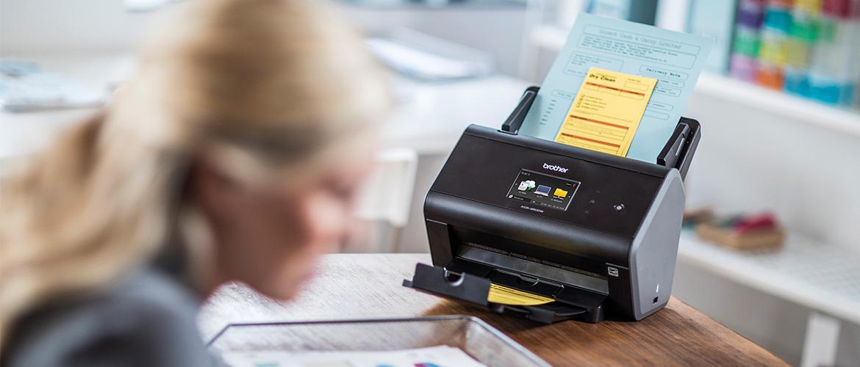 Frau an Schreibtisch scannt Rechnungen