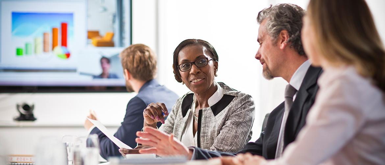 Vier Menschen im Meeting-Raum besprechen eine Präsentation.